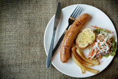Grilled sausages with salad. On white plate Stock Image
