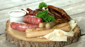 Grilled sausages with sauce. Food on wooden board stock footage