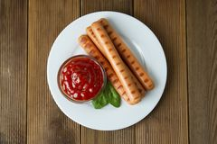 Grilled sausages with sauce ketchup on a wooden table. Fast food stock photography