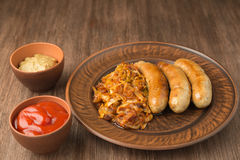 Grilled sausages with sauerkraut, mustard and tomato sauce. Royalty Free Stock Image