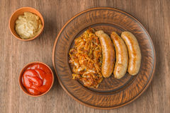 Grilled sausages with sauerkraut, mustard and tomato sauce. The view from the top. Royalty Free Stock Images