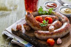 Grilled sausages served on wood board Royalty Free Stock Photos