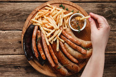 Grilled sausages served on wooden table, fat food. Oktoberfest meal, German food. Unrecognizable person eating french fries and tasty grilled sausages with Stock Photos