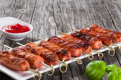 Grilled sausages on skewers with tomato sauce, top view Stock Photo