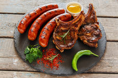 Grilled sausages and steak on the bone barbecue Stock Photography