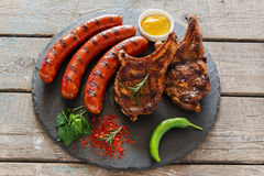 Grilled sausages and steak on the bone barbecue Royalty Free Stock Images
