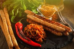 Grilled sausages and stewed cabbage with a mug of beer on a wood Stock Image