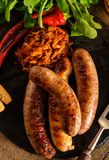 Grilled sausages and stewed cabbage with a mug of beer on a wood Royalty Free Stock Images