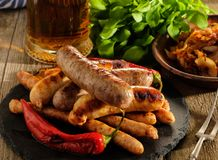 Grilled sausages and stewed cabbage with a mug of beer on a wood Stock Photography
