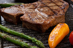 Grilled Sausages and T-Bone Steak. Summer grill - grilled sausages and T-bone steak - on griddle Royalty Free Stock Photo