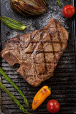 Grilled Sausages and T-Bone Steak. Summer grill - grilled sausages and T-bone steak - on griddle Royalty Free Stock Photography