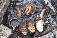 Grilled sausages, toast and  and cup of coffee on campfire Stock Images