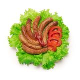 Grilled sausages with tomato and green salad. stock photos