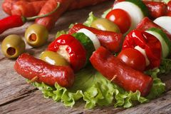 Grilled sausages with tomato, olives, chili, onions on skewers Stock Photos
