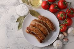 Grilled sausages with tomatoes, sunflower oil and garlic on a light background. top view stock images