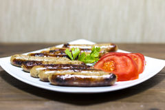 Grilled sausages. With tomatoes on wooden desk Stock Photography