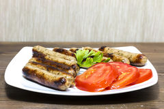 Grilled sausages. With tomatoes on wooden desk Stock Images