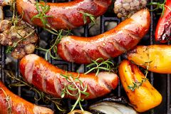 Grilled sausages and vegetables with addition spices and fresh herbs on a grill plate. Top view stock photos