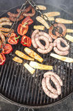 Grilled sausages and vegetables on a barbecue. Royalty Free Stock Images