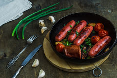 Grilled sausages with vegetables in a frying pan. Grilled sausages with vegetables and herbs in a frying pan Royalty Free Stock Image