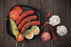 Grilled sausages and vegetables. Grilled german sausages and vegetables in grilling pan Stock Images