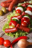 Grilled sausages with vegetables and ingredients closeup Stock Images