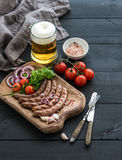 Grilled sausages with vegetables on rustic serving Stock Photo