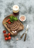 Grilled sausages with vegetables on rustic serving Stock Image