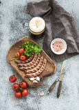Grilled sausages with vegetables on rustic serving board and mug of light beer over grunge  backdrop. Royalty Free Stock Image