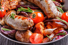 Grilled sausages and vegetables  in  rustic style. Stock Photos