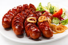 Grilled sausages. And vegetables on white background royalty free stock photography
