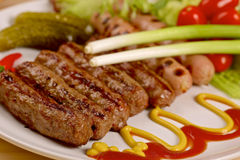 Grilled sausages with vegetables on a white plate Stock Images