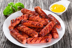 Grilled sausages on a white dish, close-up. Grilled sausages decorated with basil leaves on a white dish on an old rustic table, mustard in a gravy boat, studio royalty free stock photo