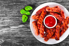 Grilled sausages on a white dish, top view Royalty Free Stock Photo