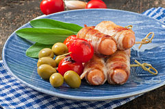 Grilled sausages wrapped in strips of bacon Stock Photography