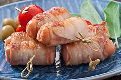 Grilled sausages wrapped in strips of bacon Royalty Free Stock Photo