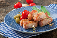 Grilled sausages wrapped in strips of bacon Stock Photo