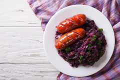 Grilled Sausageswith stewed red cabbage. horizontal top view Royalty Free Stock Images