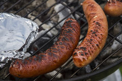 Grilled sauseges. Grilled sausages on the hot grill with your next meal - camembert Stock Image