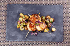 Grilled scallops with roasted young potatoes stock image