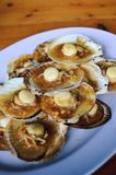 Grilled scallops topped with butter, garlic and onion Stock Photo