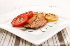 Grilled scottish kipper with rosemary, tomato and slice lemon. An a white plate Stock Images