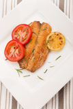 Grilled scottish kipper with rosemary, tomato and slice lemon. An a white plate Stock Image