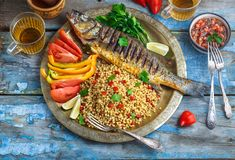 Grilled sea bass on coper plate, moroccan style.  royalty free stock photography