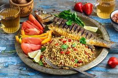 Grilled sea bass on coper plate, moroccan style.  stock photo