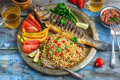 Grilled sea bass on coper plate, moroccan style.  royalty free stock photo