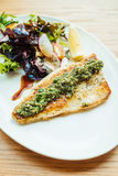 Grilled sea bass fish meat steak with vegetable. And lemon in white plate - Color Filter Processing royalty free stock photo