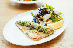 Grilled sea bass fish meat steak with vegetable. And lemon in white plate - Color Filter Processing stock photos