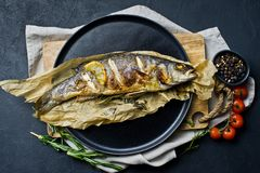 Grilled sea bass on Kraft paper in a black plate. Black background, top view. stock photos