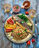 Grilled sea bass with ptitim and vegetables on copper plate, copy space.  royalty free stock photo
